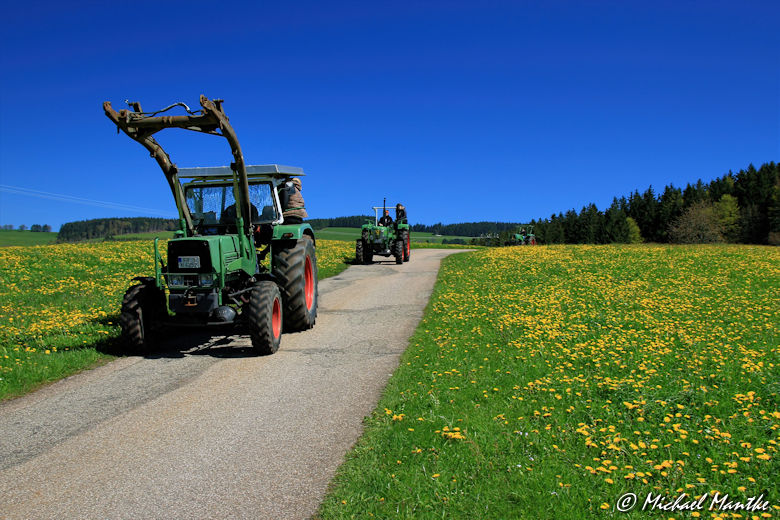 Traktoren auf Wanderweg zwischen Wiesen