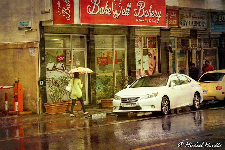 Dubai im Regen Fußgänger mit Schirm und Auto