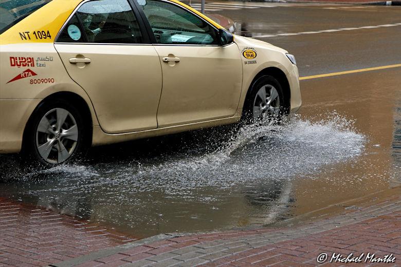 Dubai im Regen Taxi fährt durch Pfütze